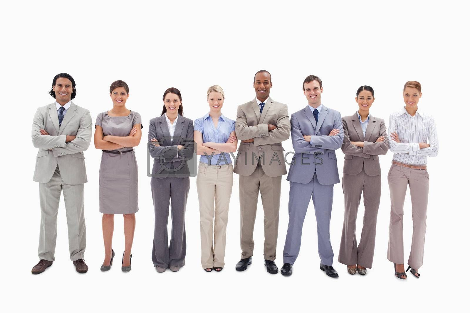 Smiling business team crossing their arms side by side against white background
