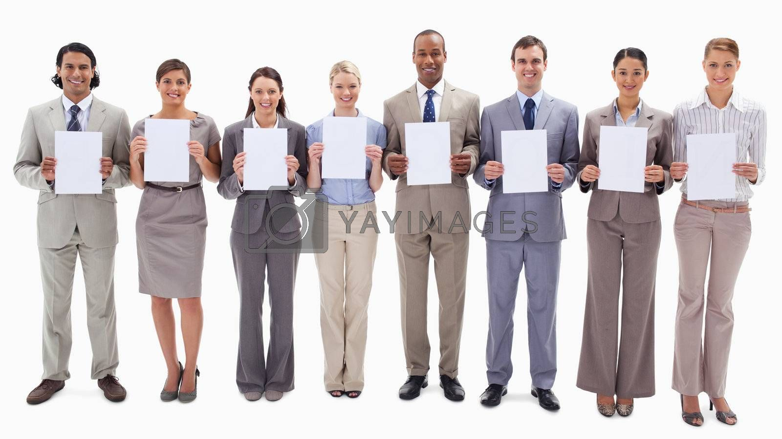 Business people smiling while holding white support for letters against white background