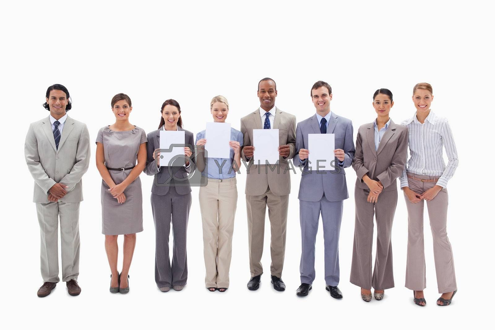 Happy business people holding four white supports for letters against white background