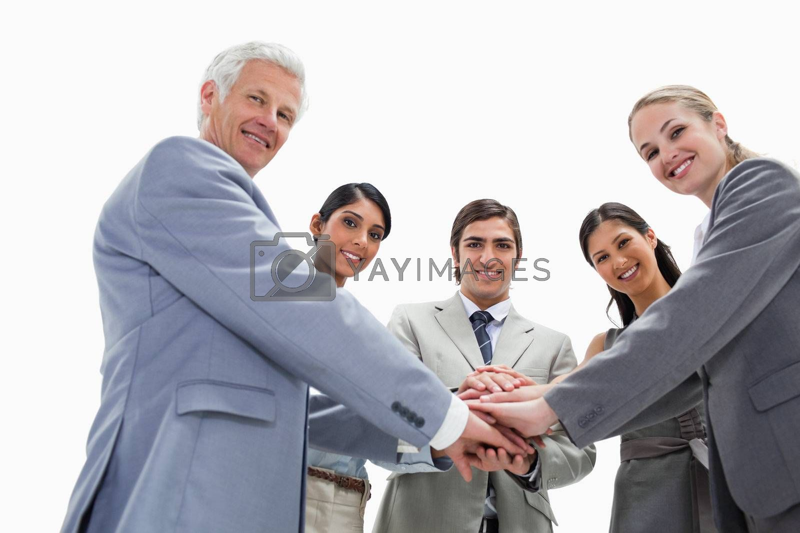 Happy team putting their hands on each others against white background