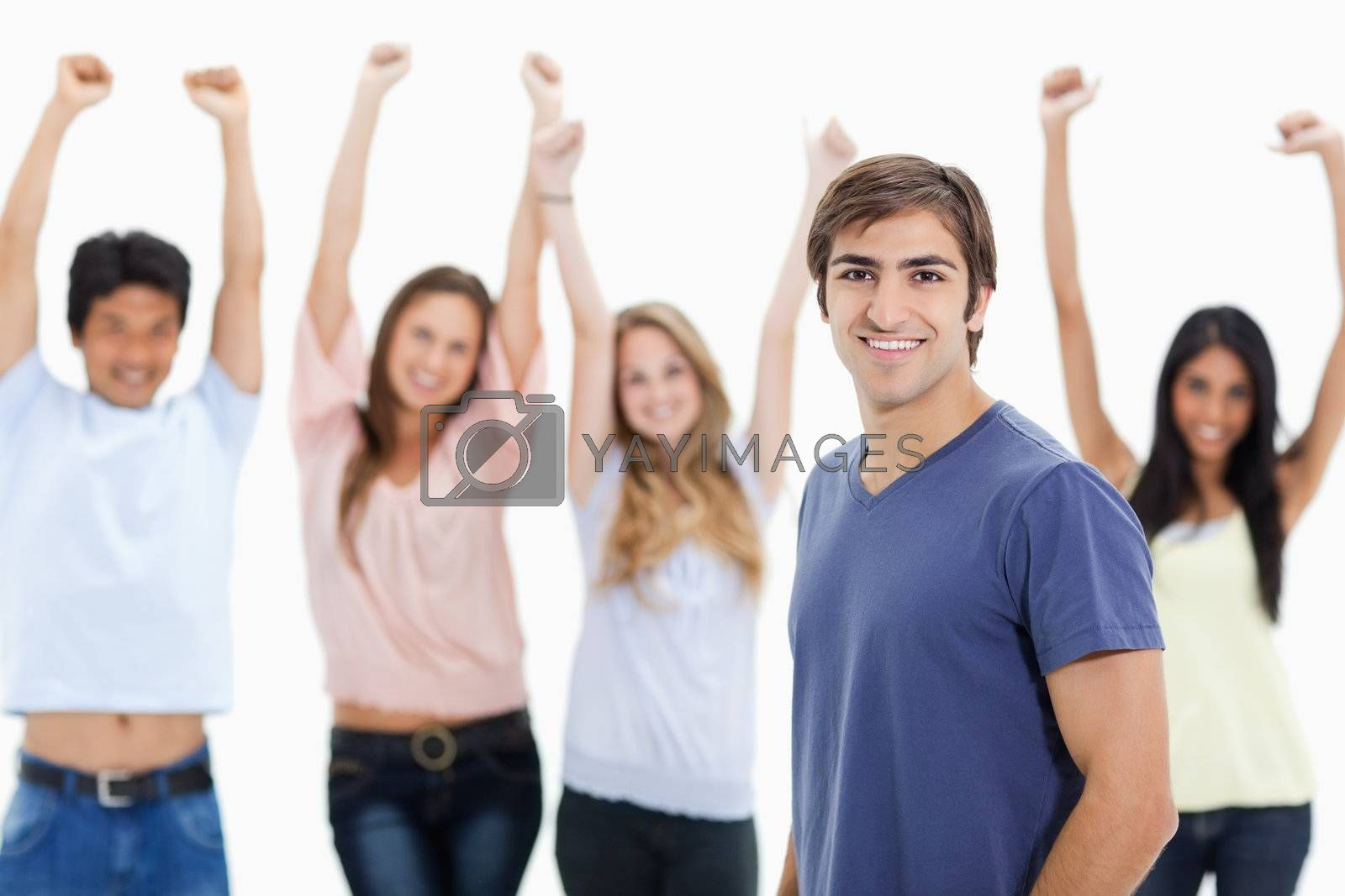 Smiling man with people behind him raising their arms against white background