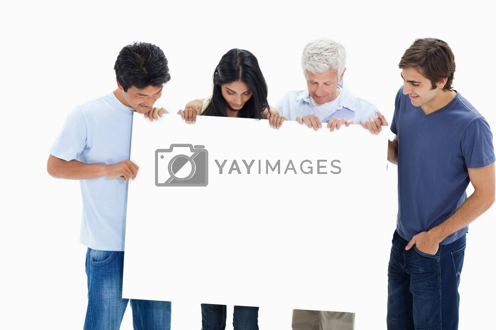 People in jeans holding and watching a big sign against white background