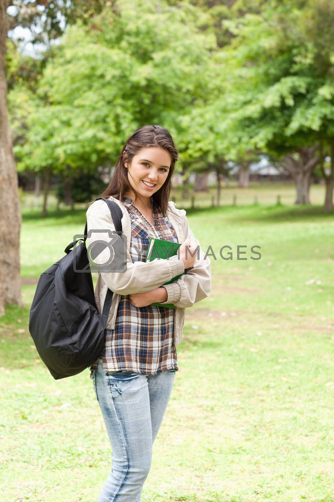 Young student holding textbook while posing in a park