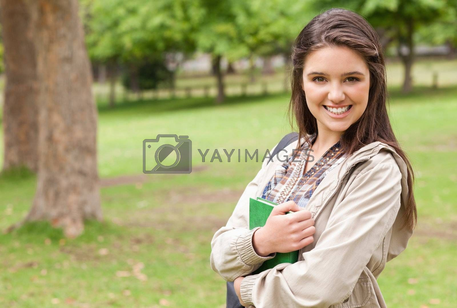 Portrait of a young student holding textbook while posing in a park