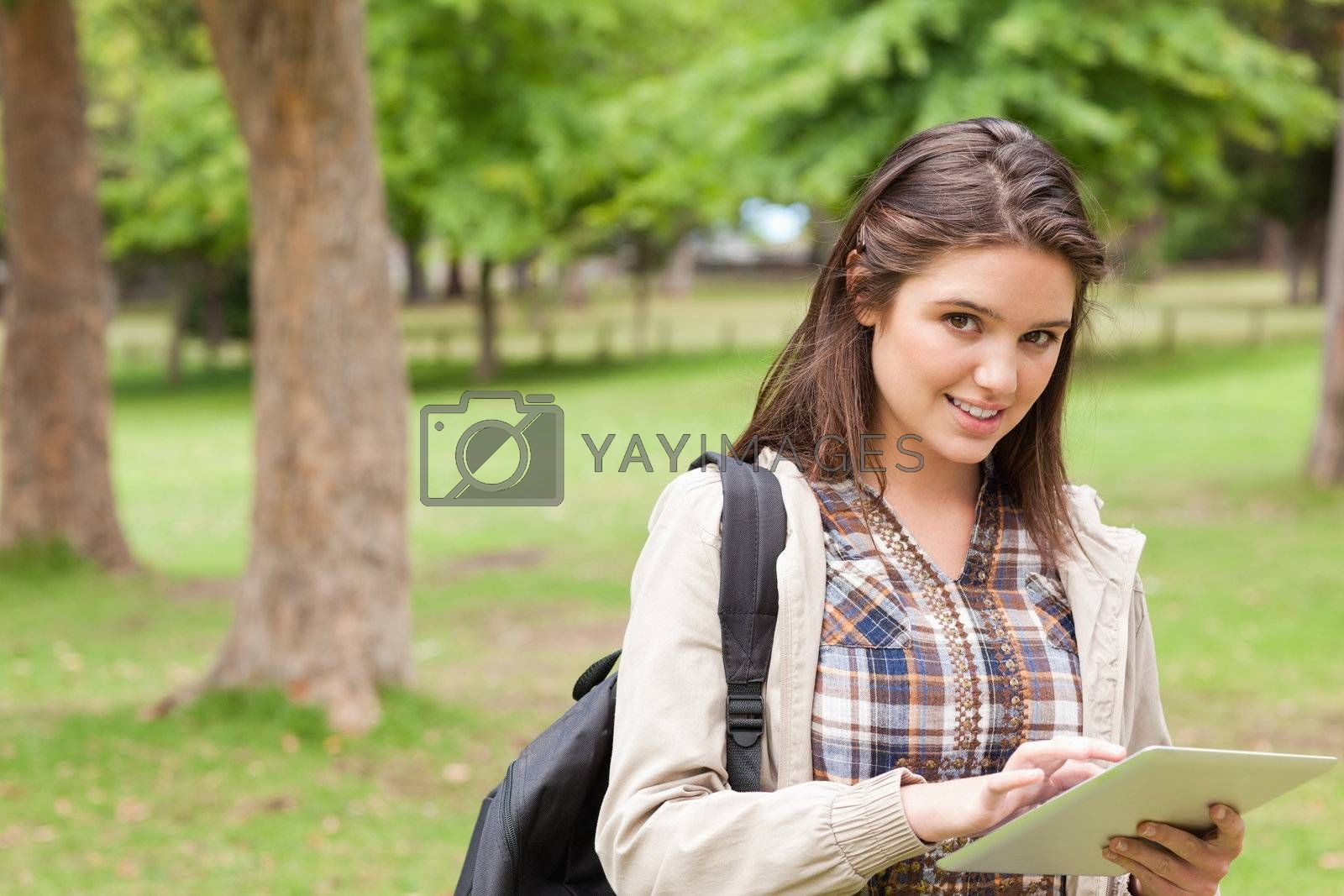 Portrait of a first-year female student using a touch pad in a park