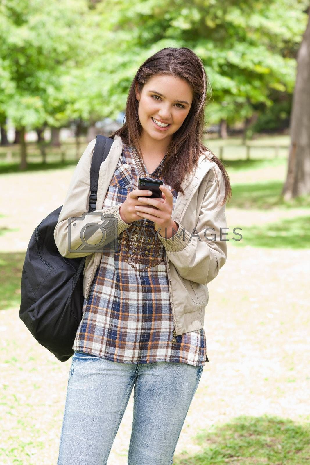 Young smiling student using a smartphone in a park