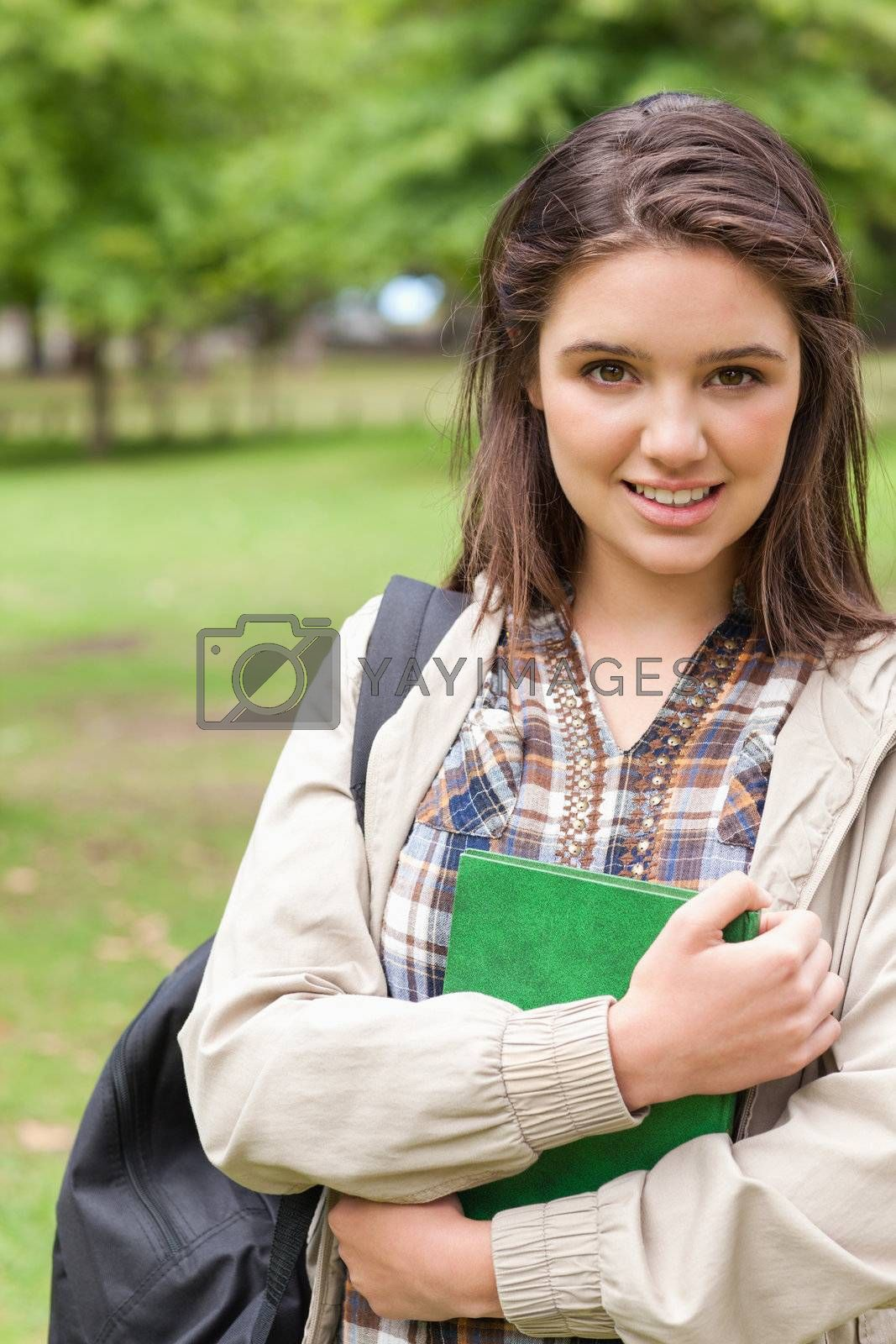Portrait of a cute first-year student holding a textbook while posing in a park