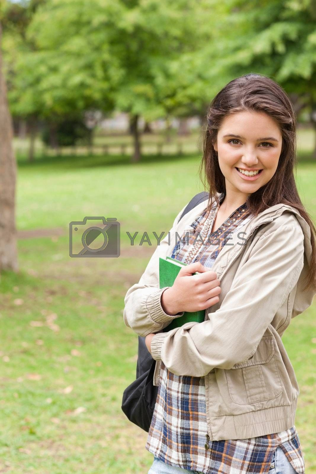 Portrait of a young smiling student holding textbook while posing in a park