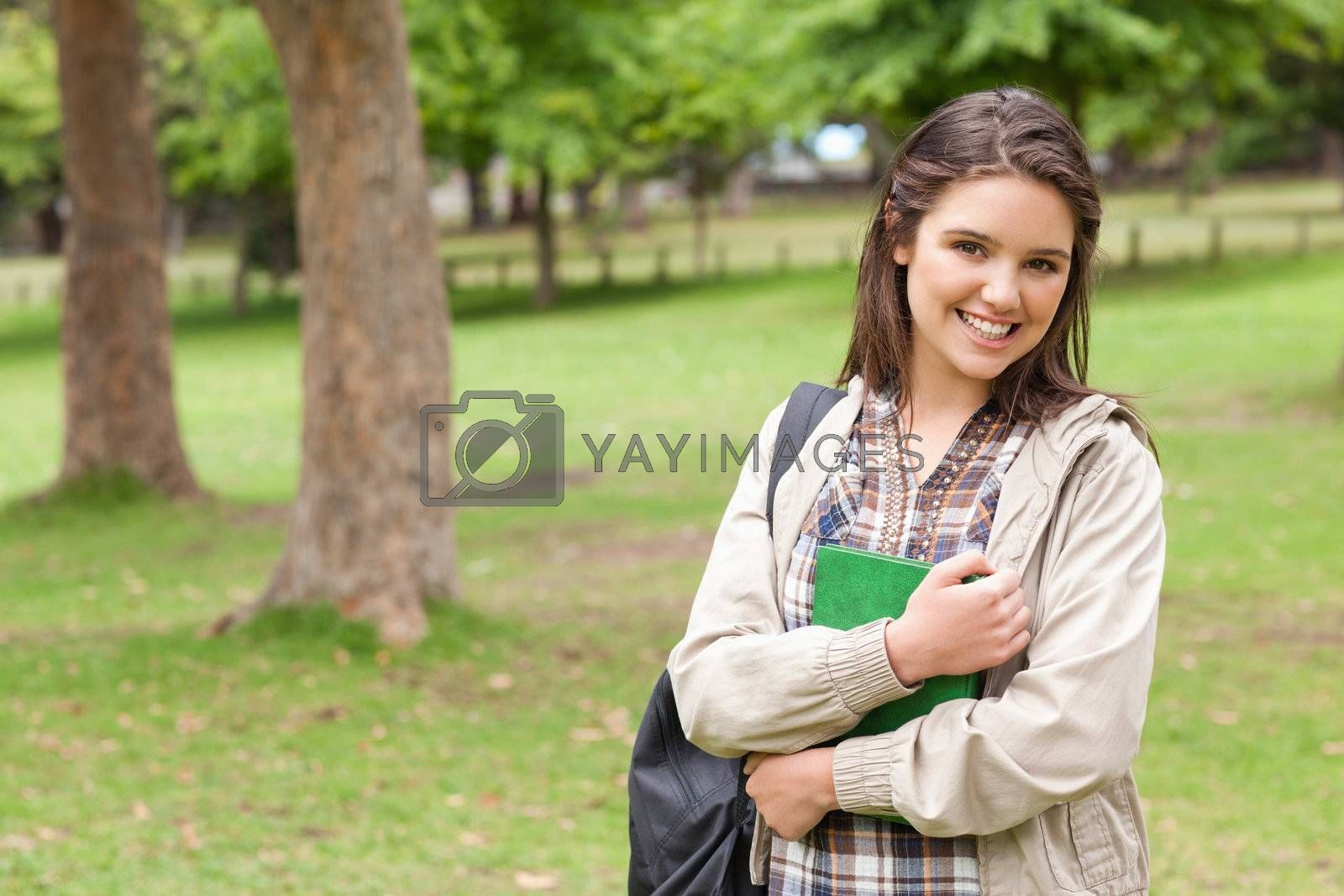Portrait of a cute student holding textbook while posing in a park