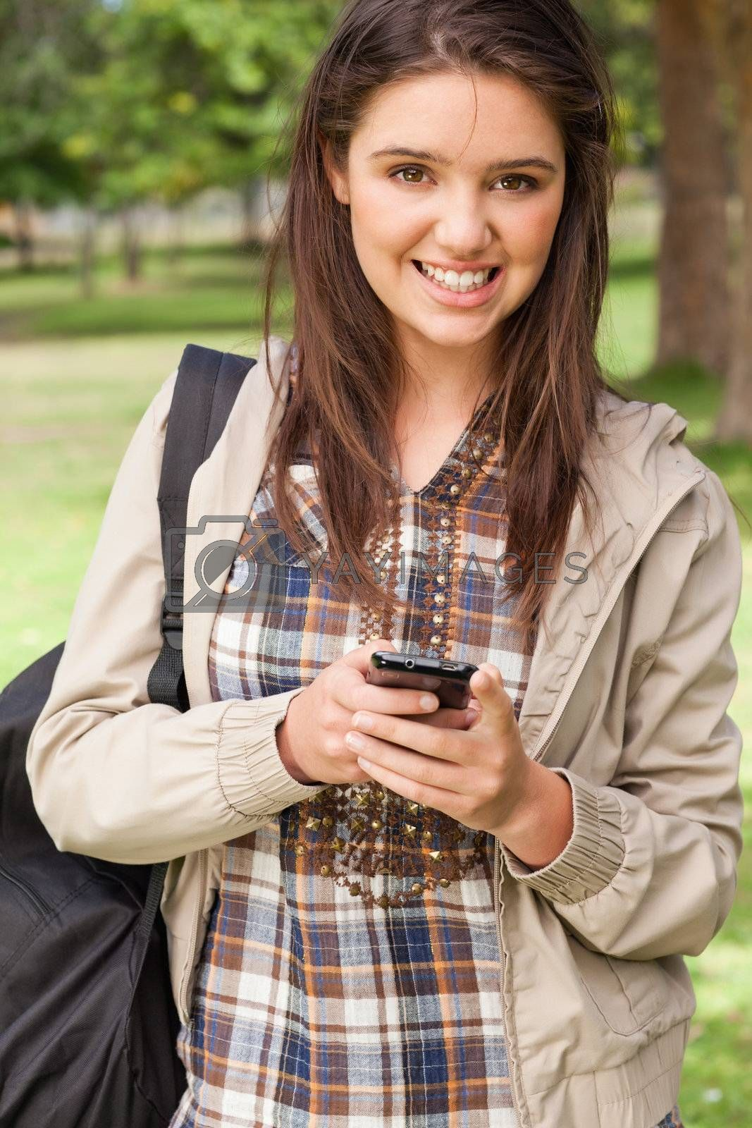 Portrait of a young student using a smartphone in a park