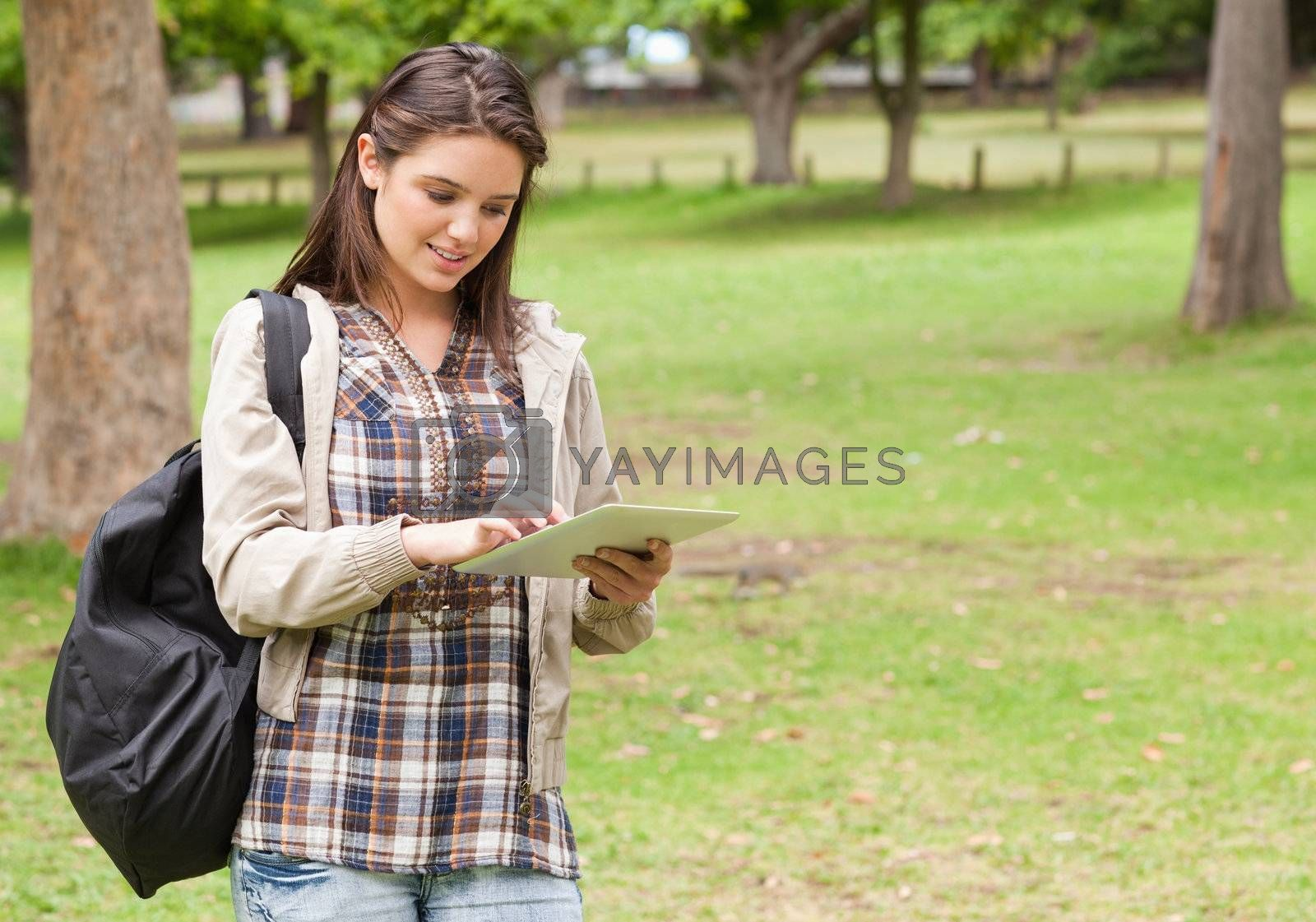 Young female student using a tactile tablet in a park