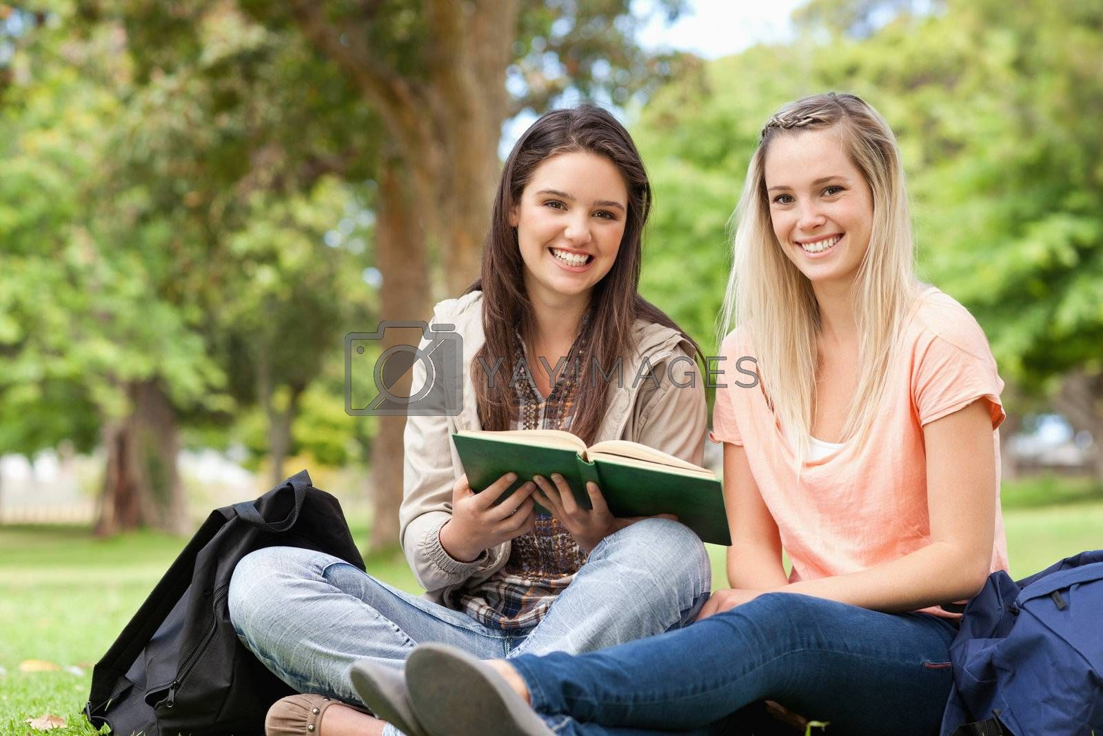 Smiling teenagers sitting while studying with a textbook in a park