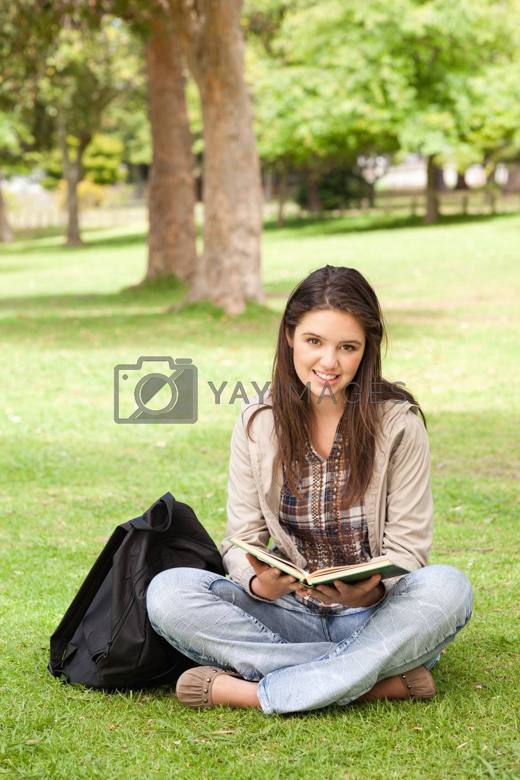 Teenager sitting with a textbook in a park while looking at camera