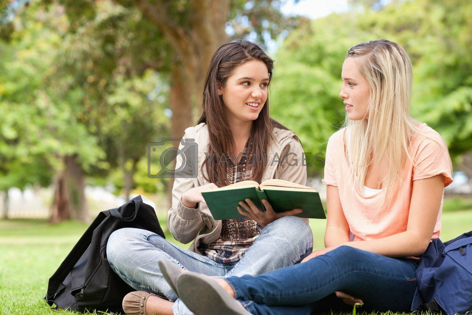 Female teenagers sitting while studying with a textbook in a park