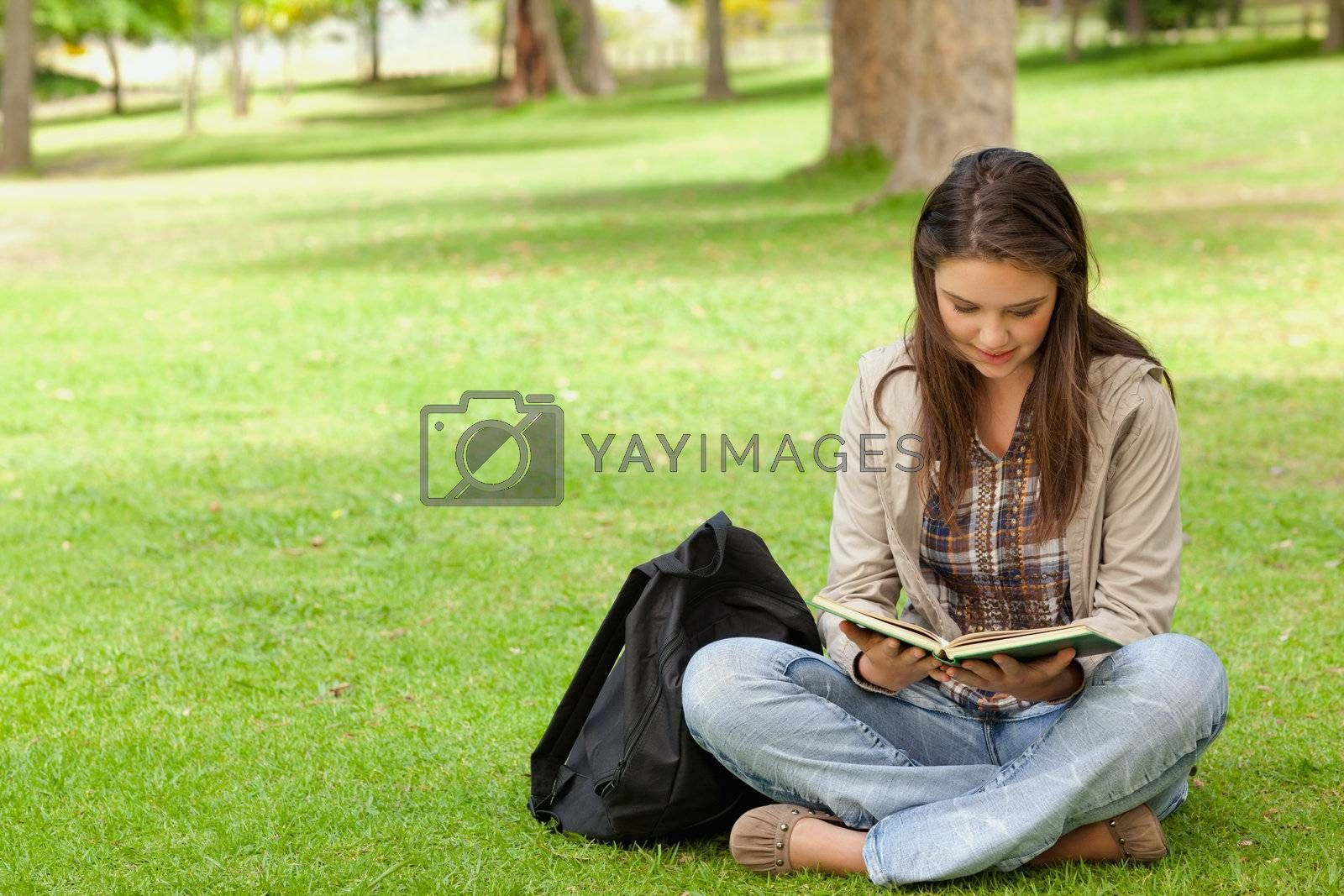 Teenager sitting while reading her textbook in a park