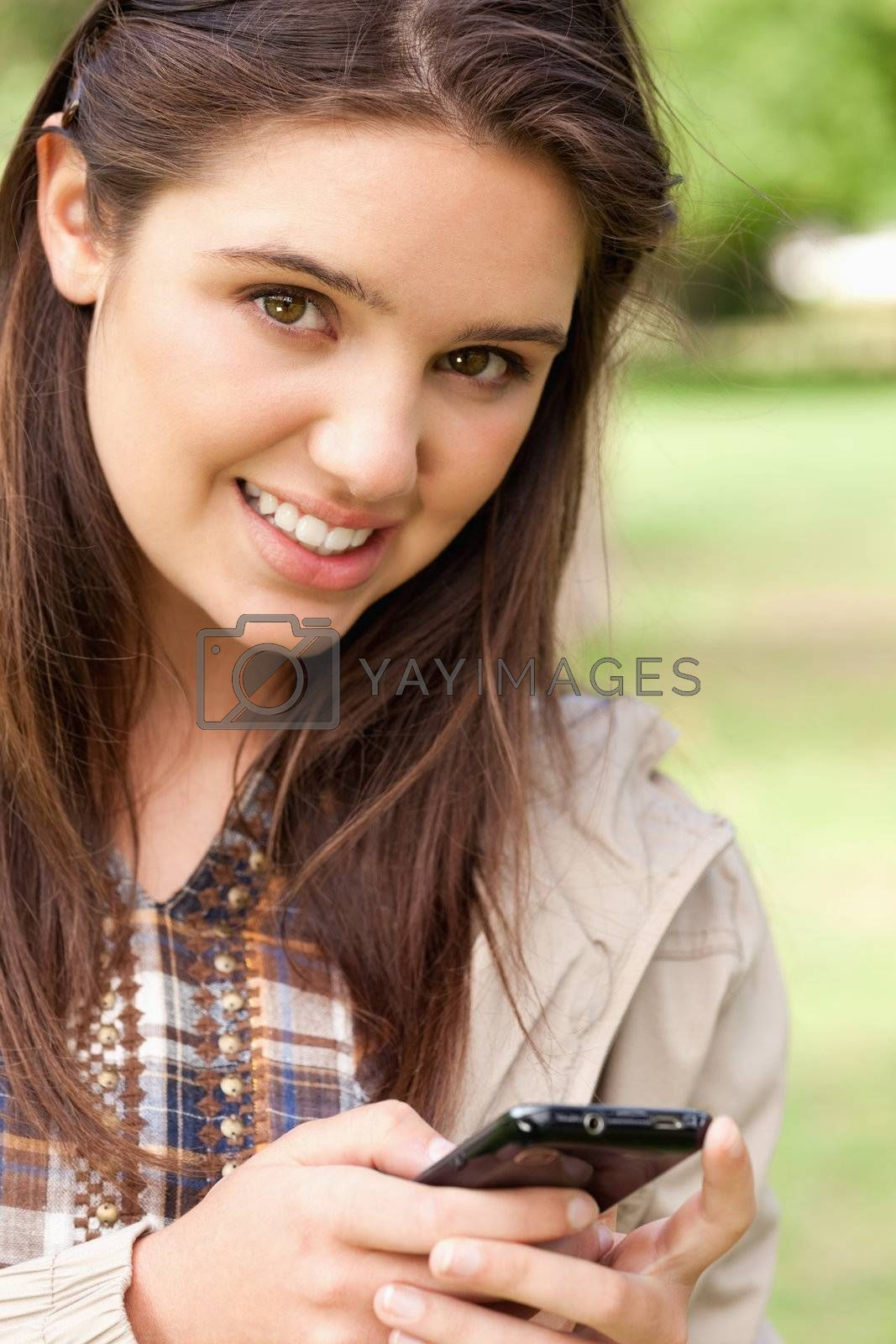 Portrait of a cute teenager using a smartphone in a park