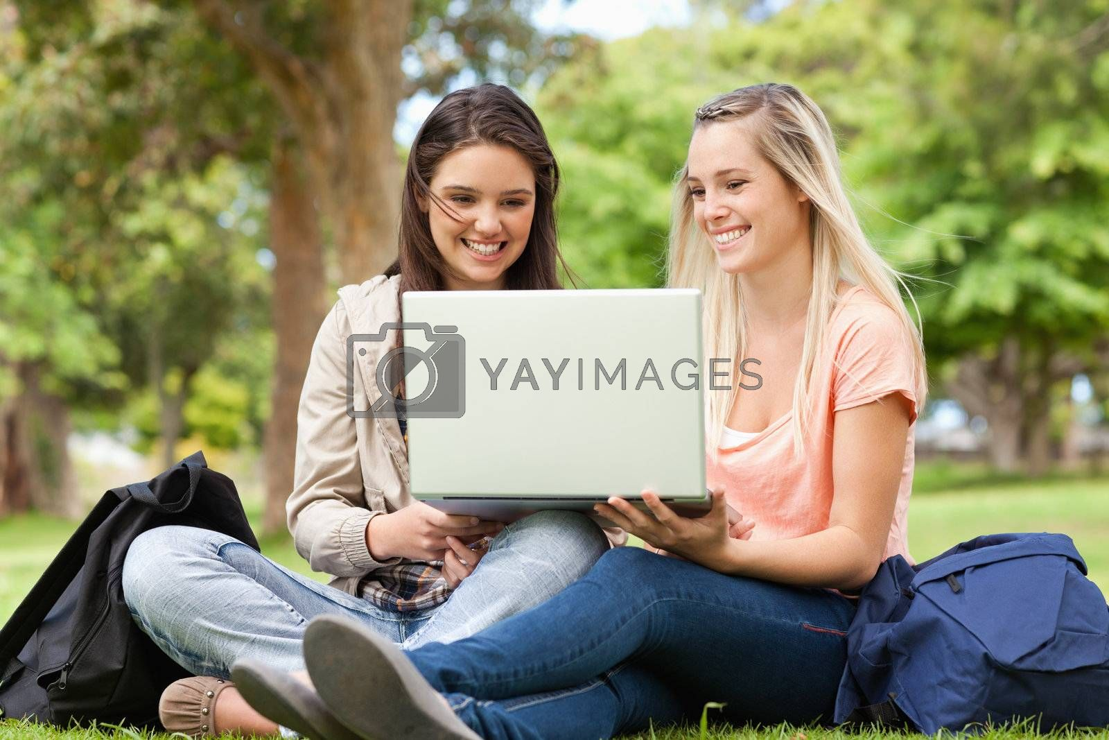 Happy teenagers sitting while using a laptop in a park