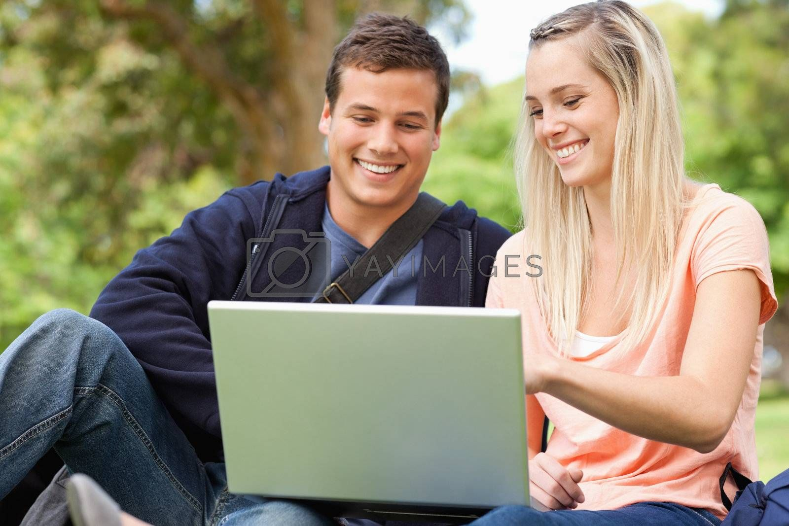 Young people sitting while using a laptop in a park
