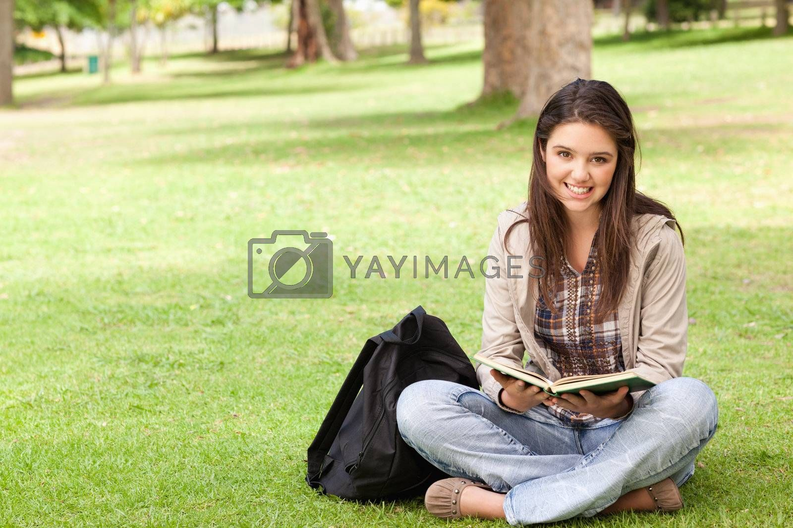 Smiling teenager sitting while holding a textbook in a park
