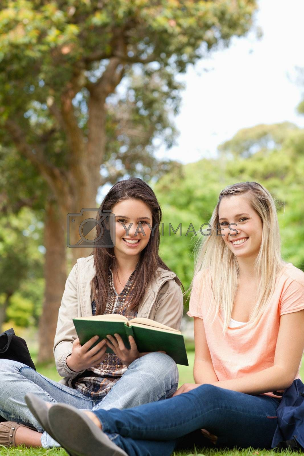 Cute teenagers sitting while studying with a textbook in a park