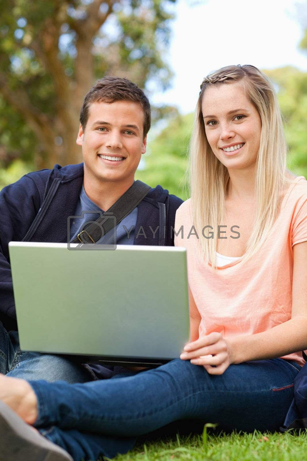 Portrait of young people laughing while sitting with a laptop in a park