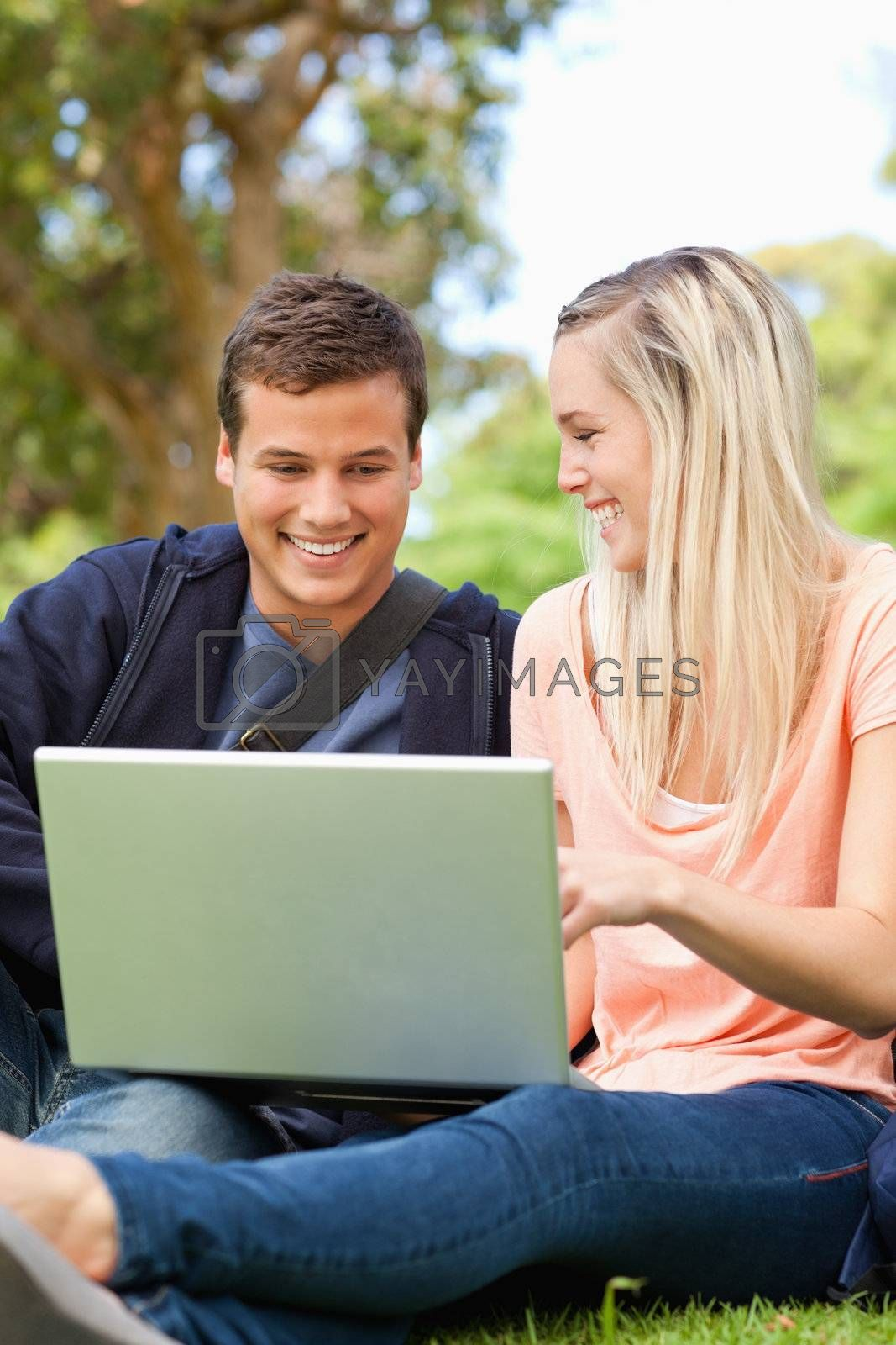 Close-up of young people laughing while sitting with a laptop in a park