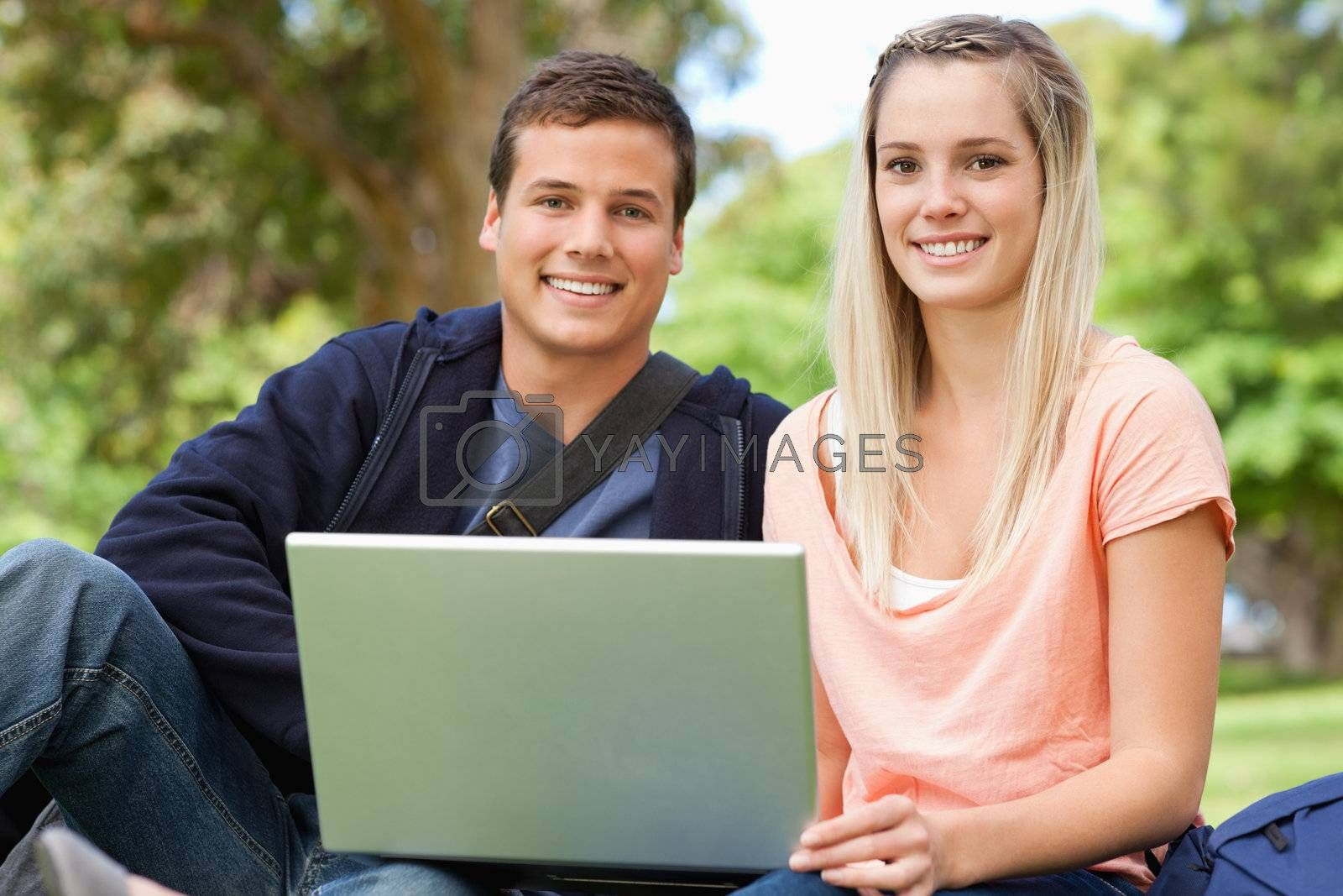Portrait of two students laughing while sitting with a laptop in a park