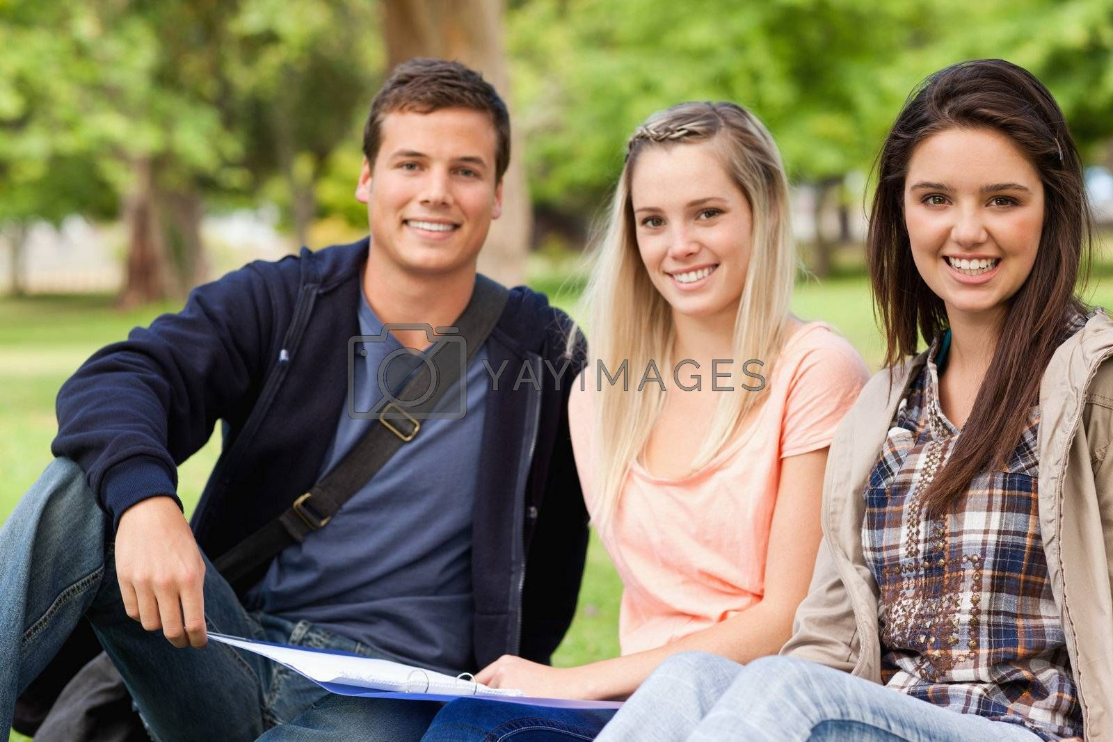Portrait of students studying together while sitting in a park