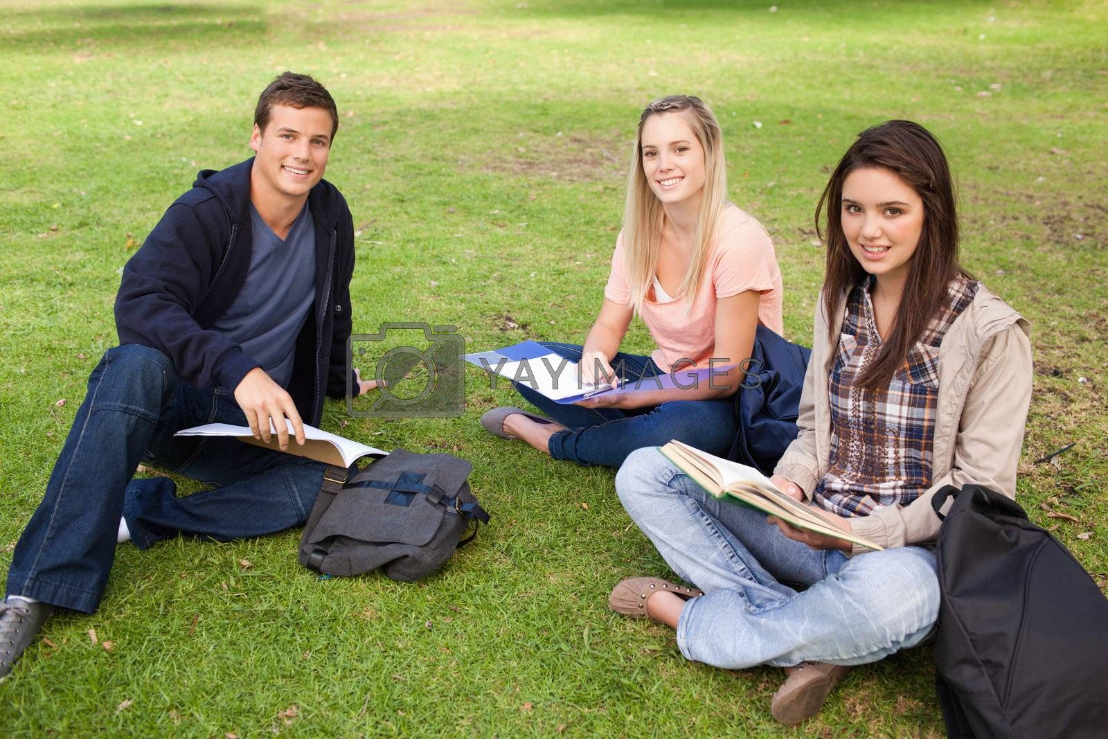 Three smiling students studying together in a park