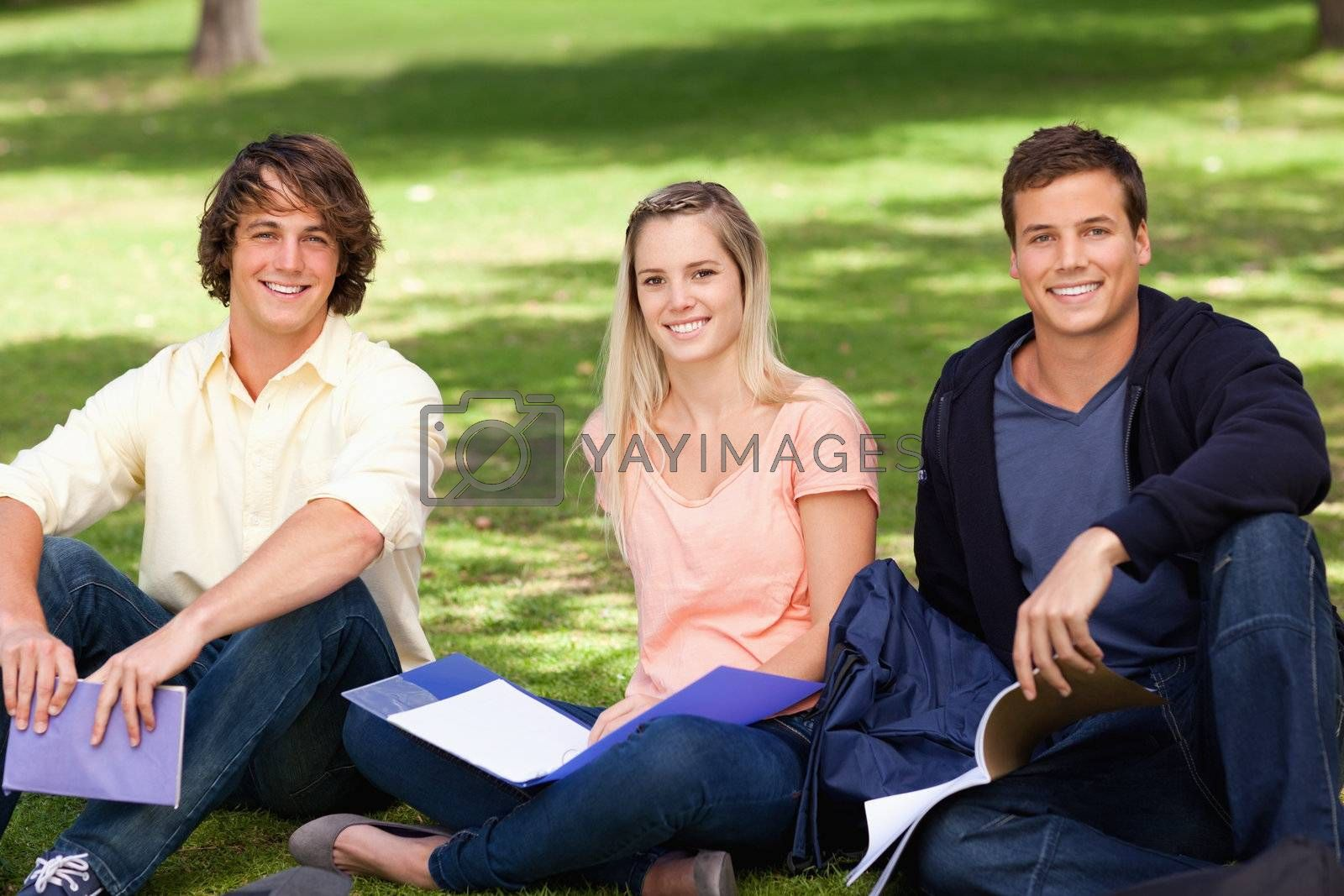 Portrait of three students in a park studying