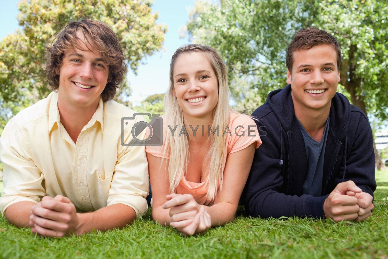 Portrait of three smiling students in a park lying on their tummy