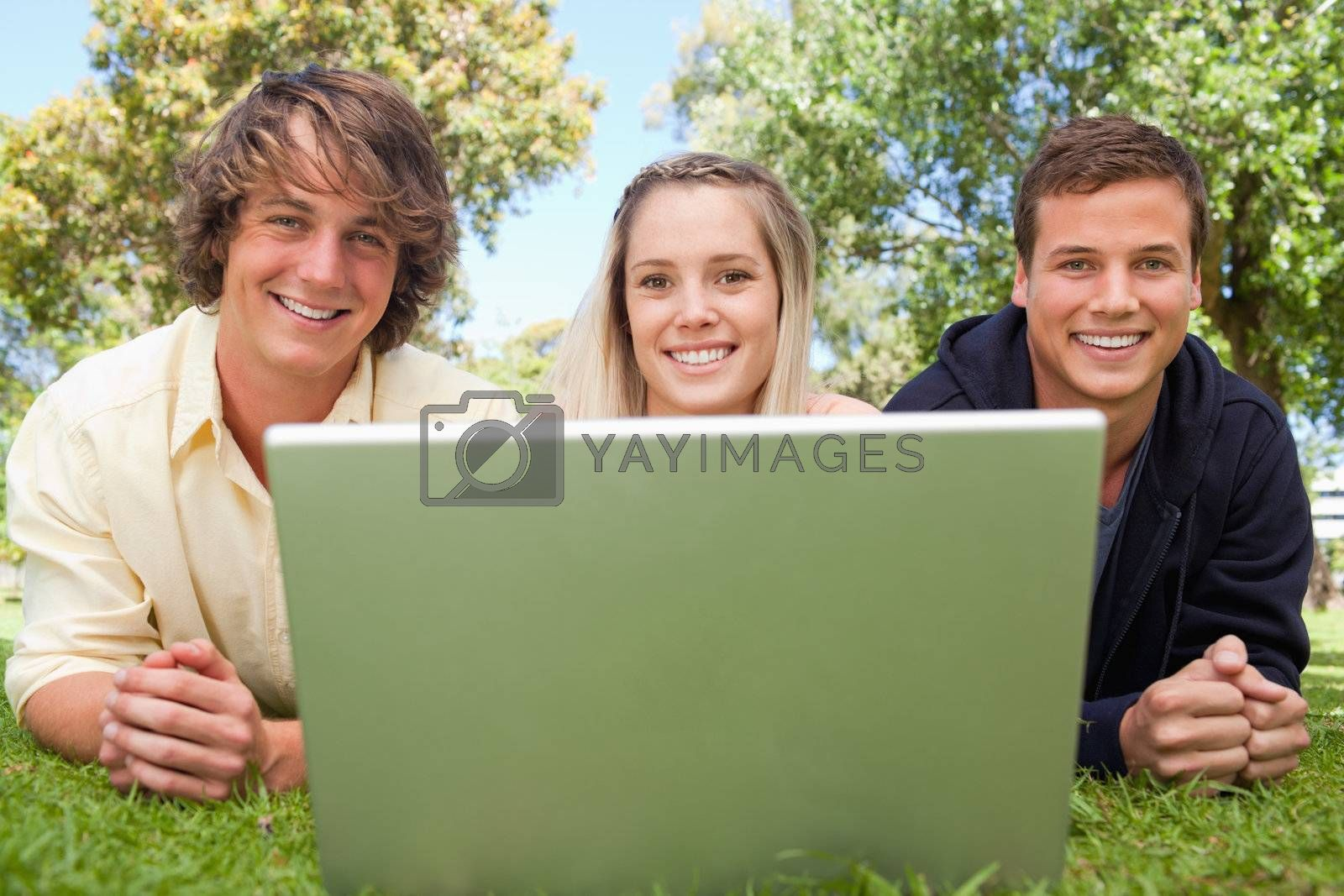 Close-up of three happy students in a park lying while using a laptop