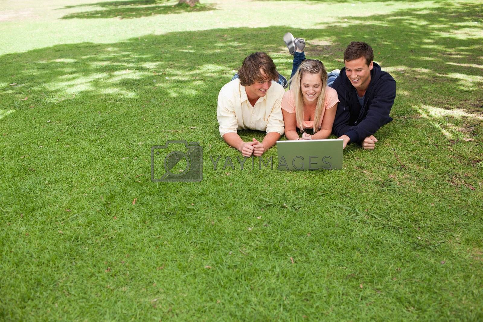 Three smiling young people in a park lying while using a laptop