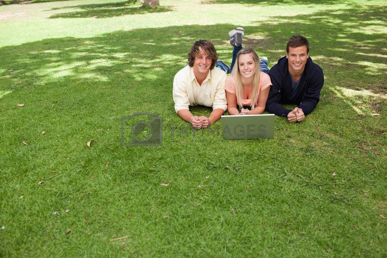 Three smiling students looking at camera in a park lying while using a laptop