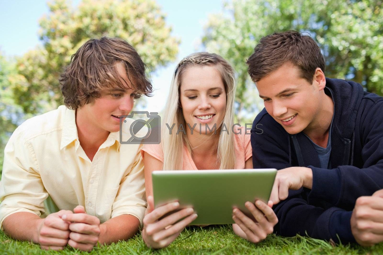 Three students using a touch pad while lying in a park
