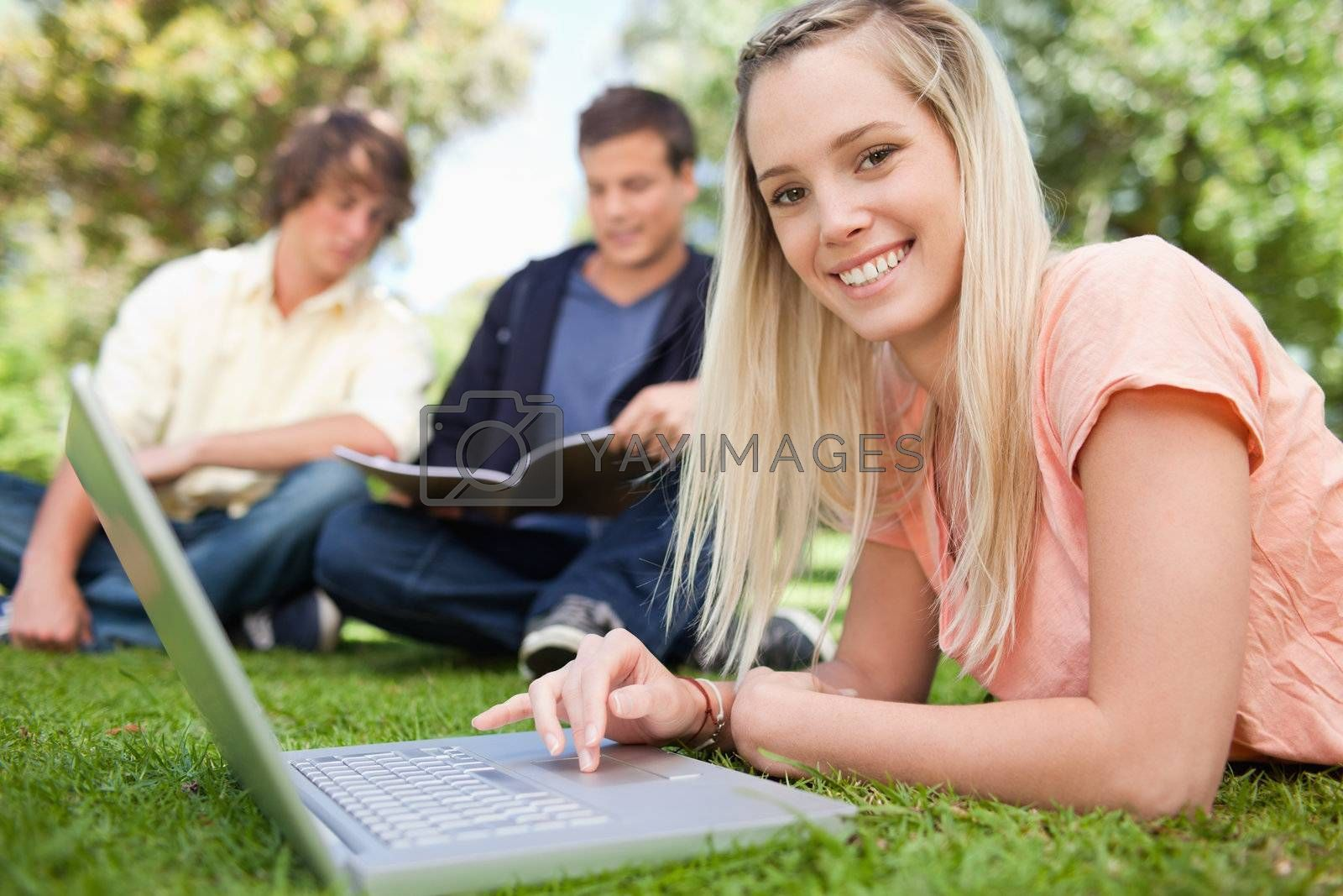 Portrait of a girl using a laptop while lying in a park with friends in background