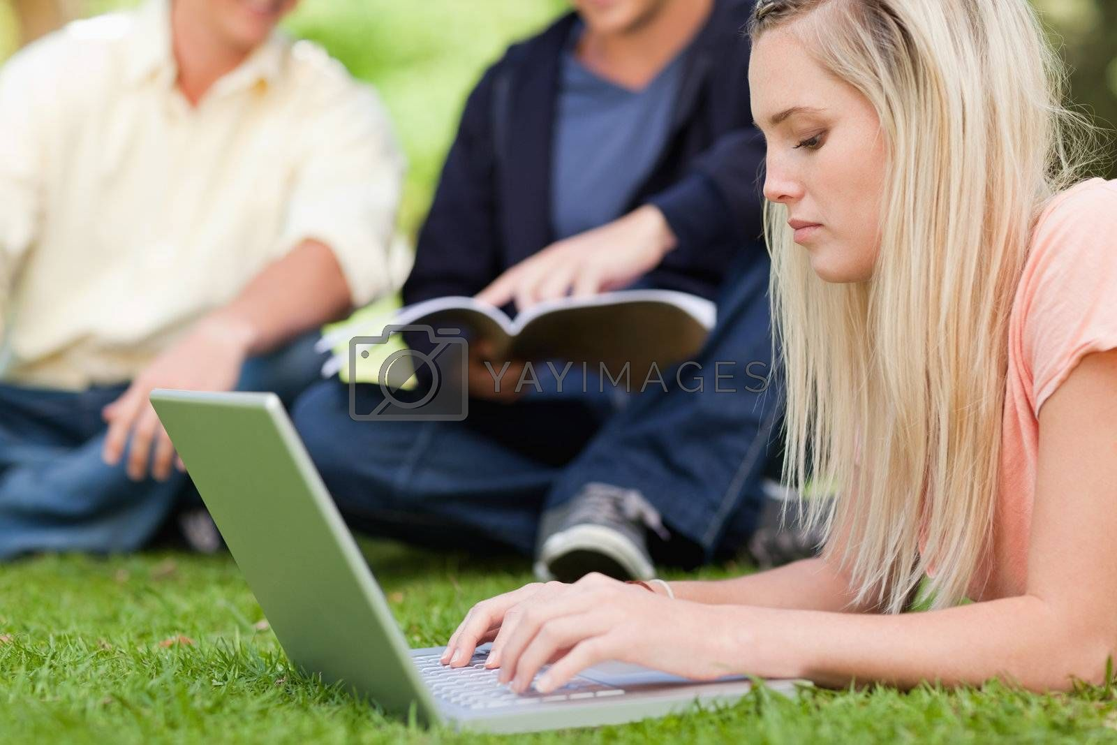 Close-up of a girl using a netbook while lying in a park with friends in background