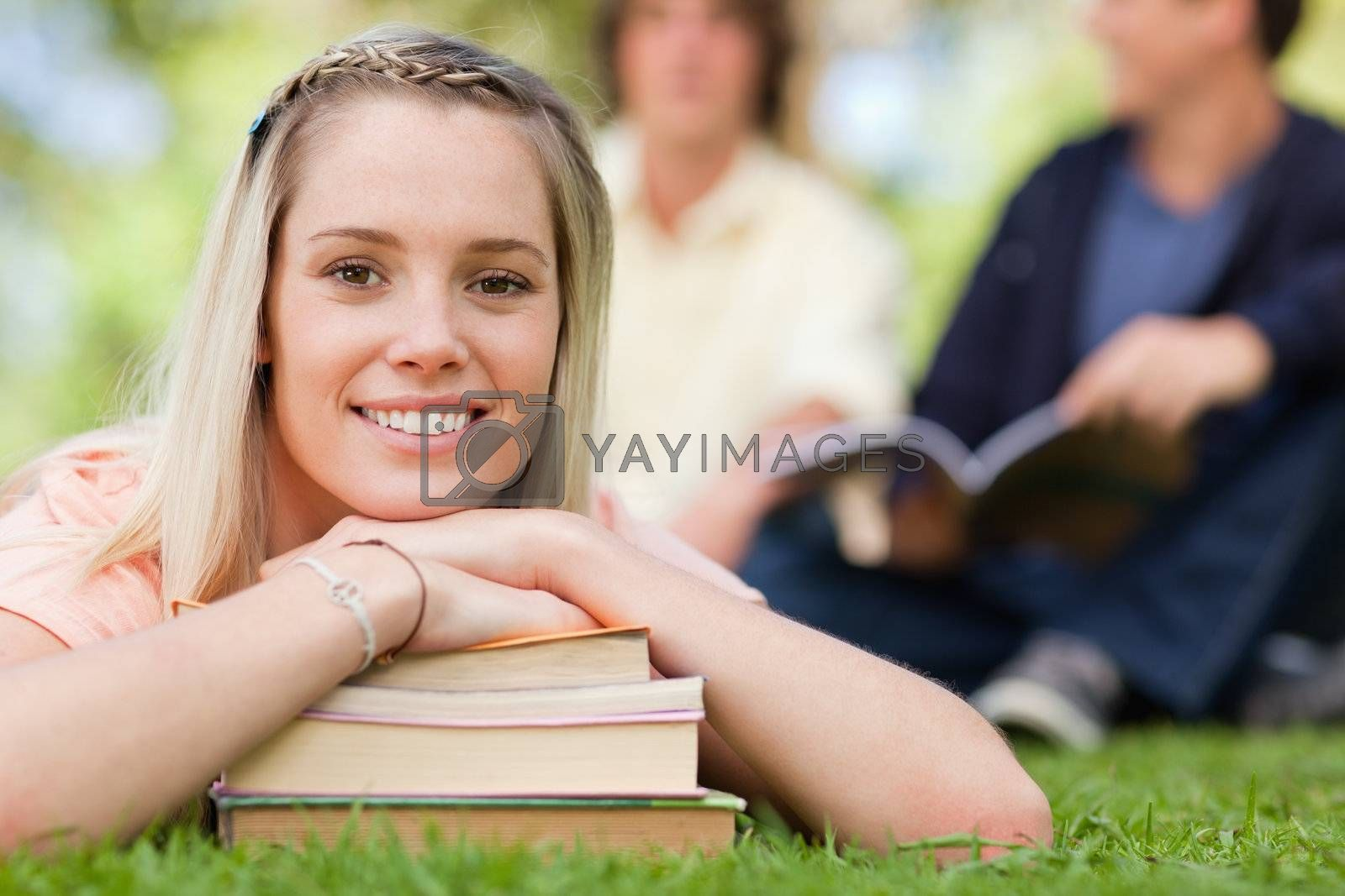 Portrait of a girl lying head on her books in a park with friends in background