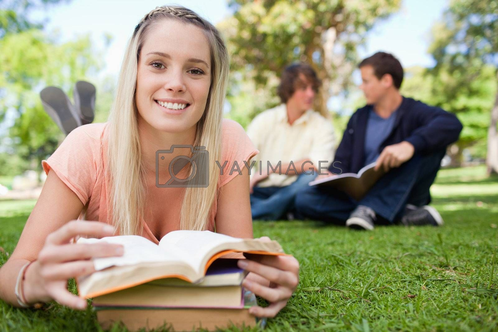 Smiling a girl lying in front of her books in a park with friends in background