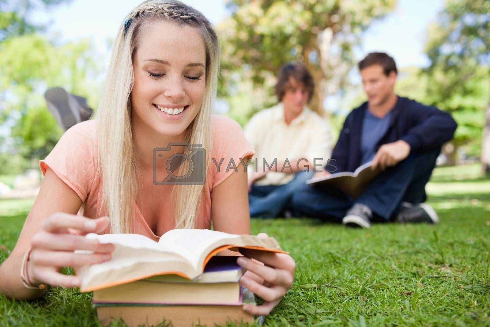 Girl lying while reading books in a park with friends in background