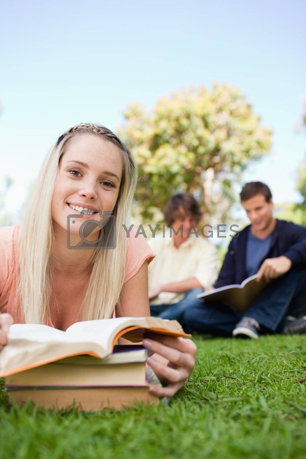Portrait of a girl lying while reading books in a park with friends in background