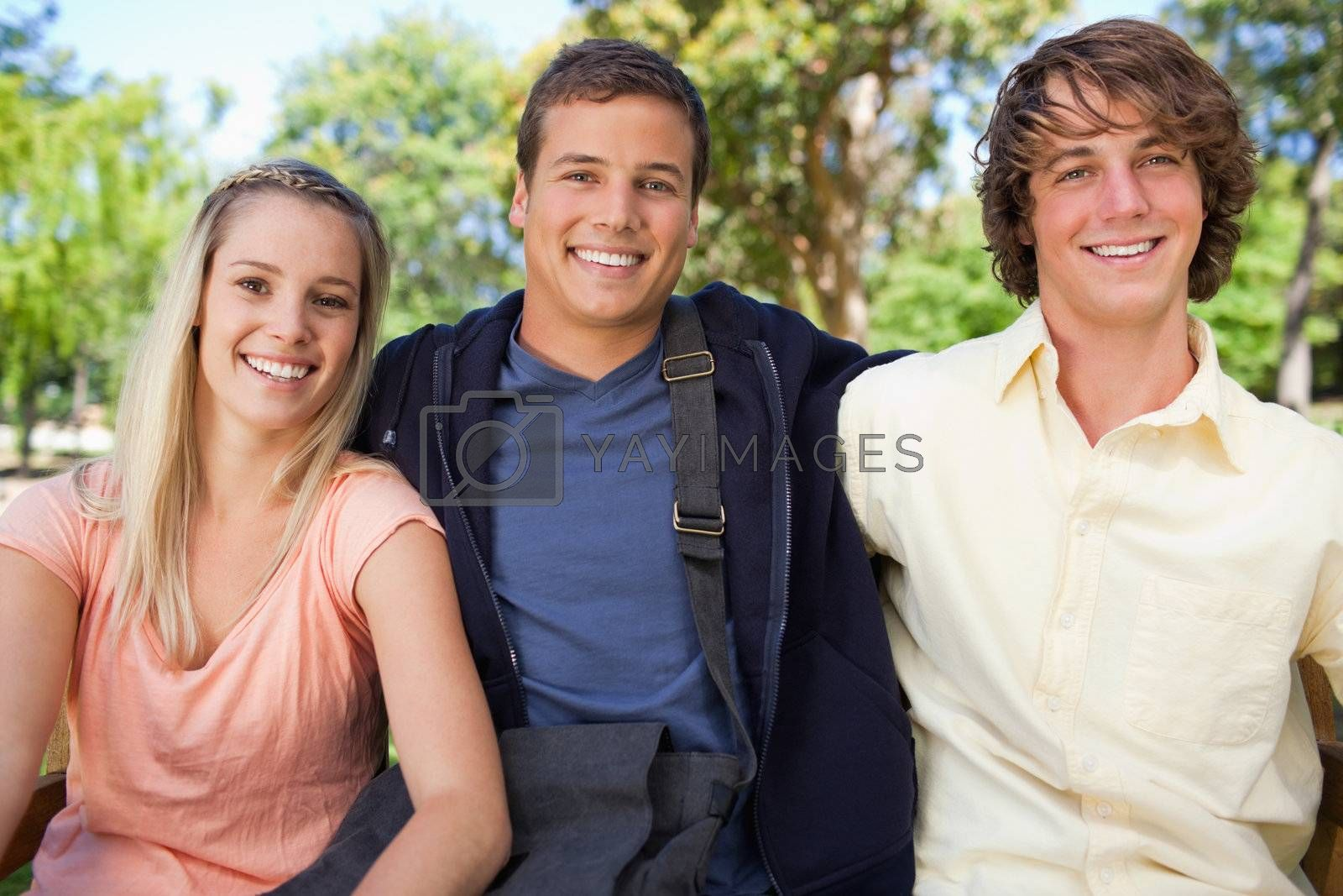 Portrait of three smiling students in a park together