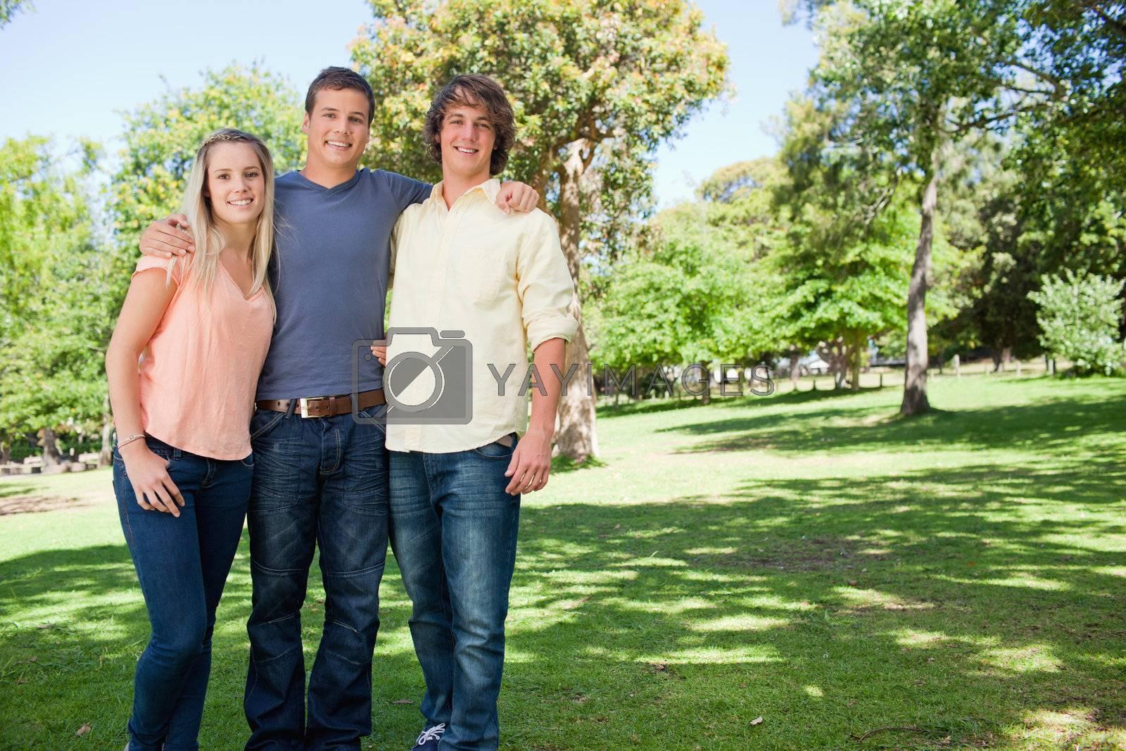 Portrait of three smiling students shoulder to shoulder in a park