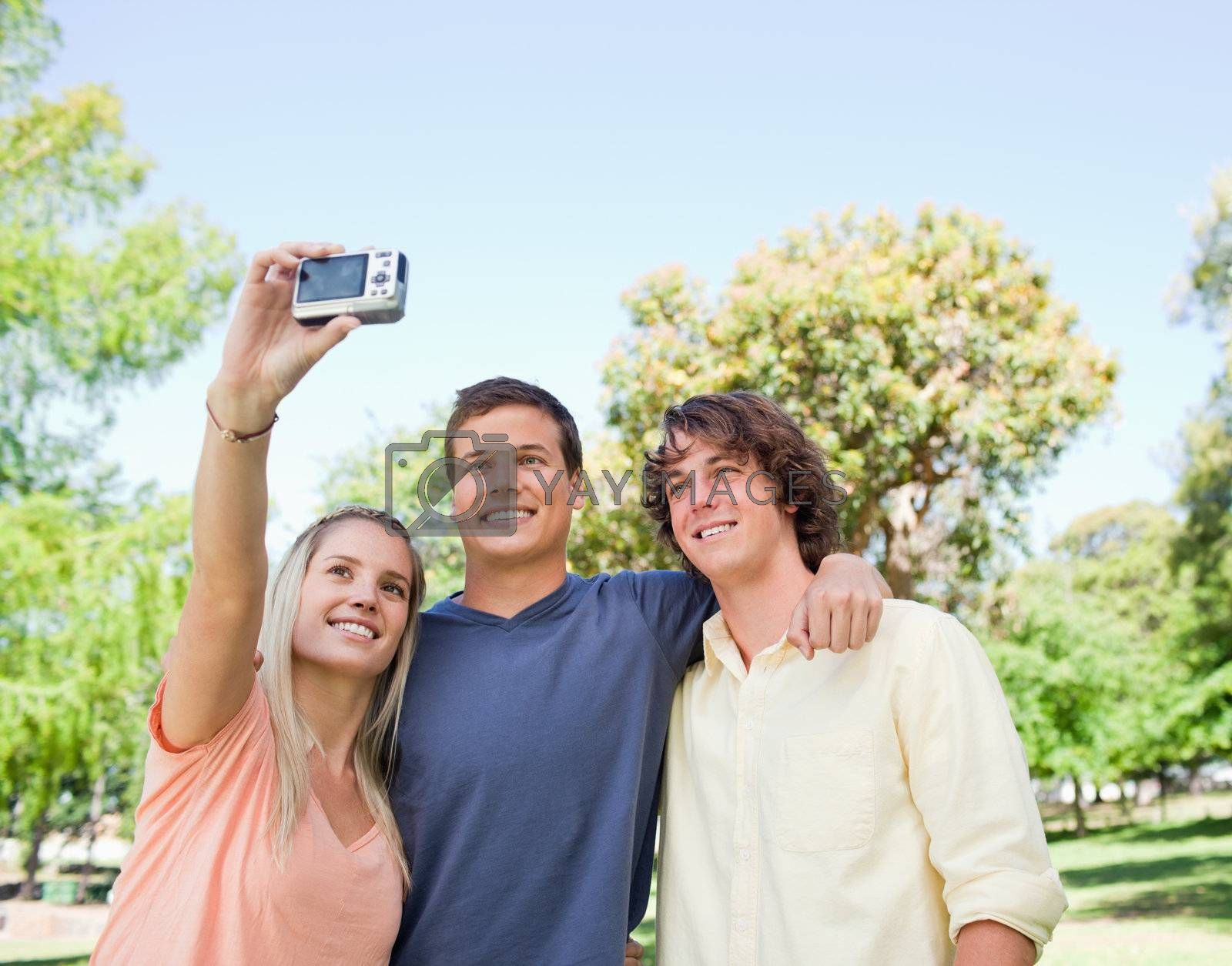 Close-up of three smiling students taking a pictures of themselves in a park