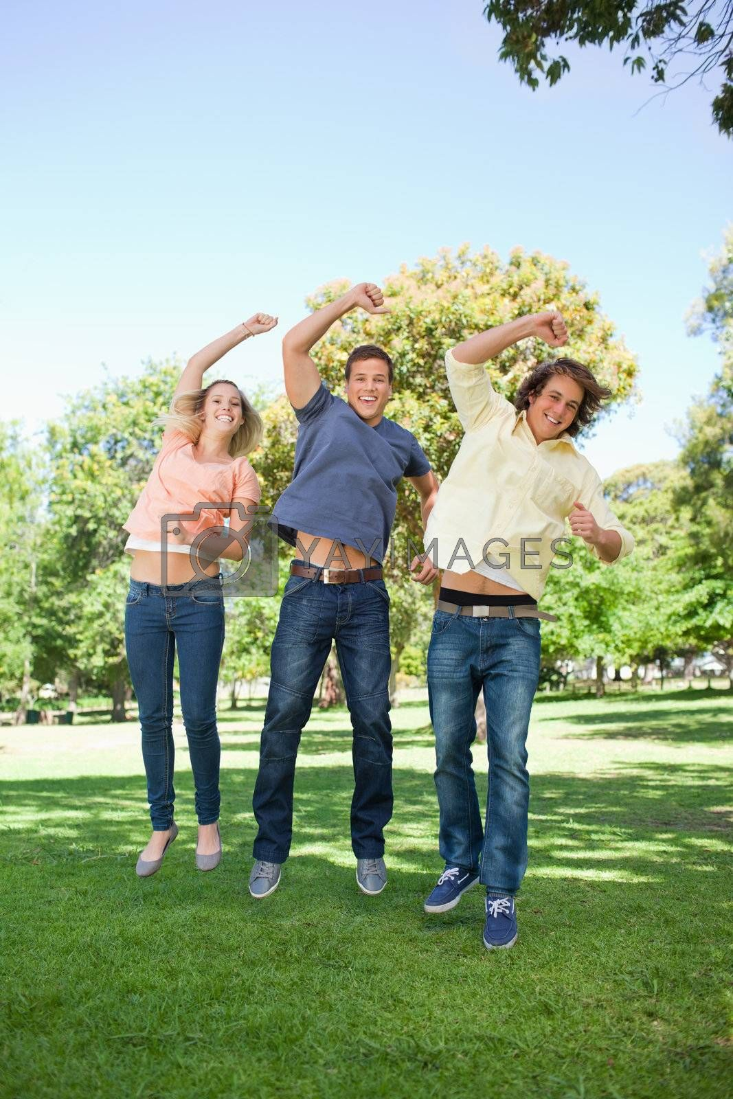 Three students jumping while raising an arm in a park