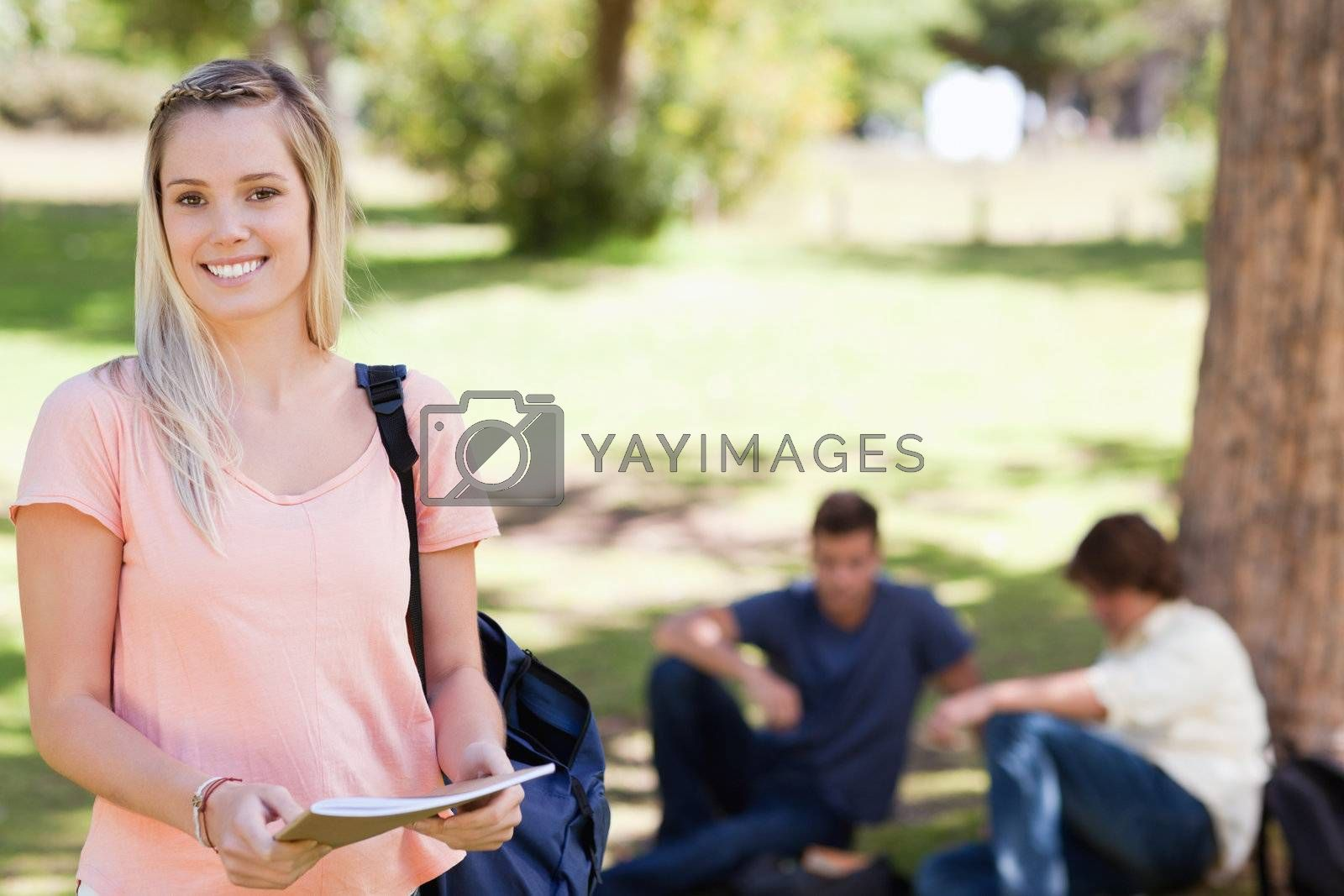 Portrait of a female student smiling while holding a textbook in a park with friends in background