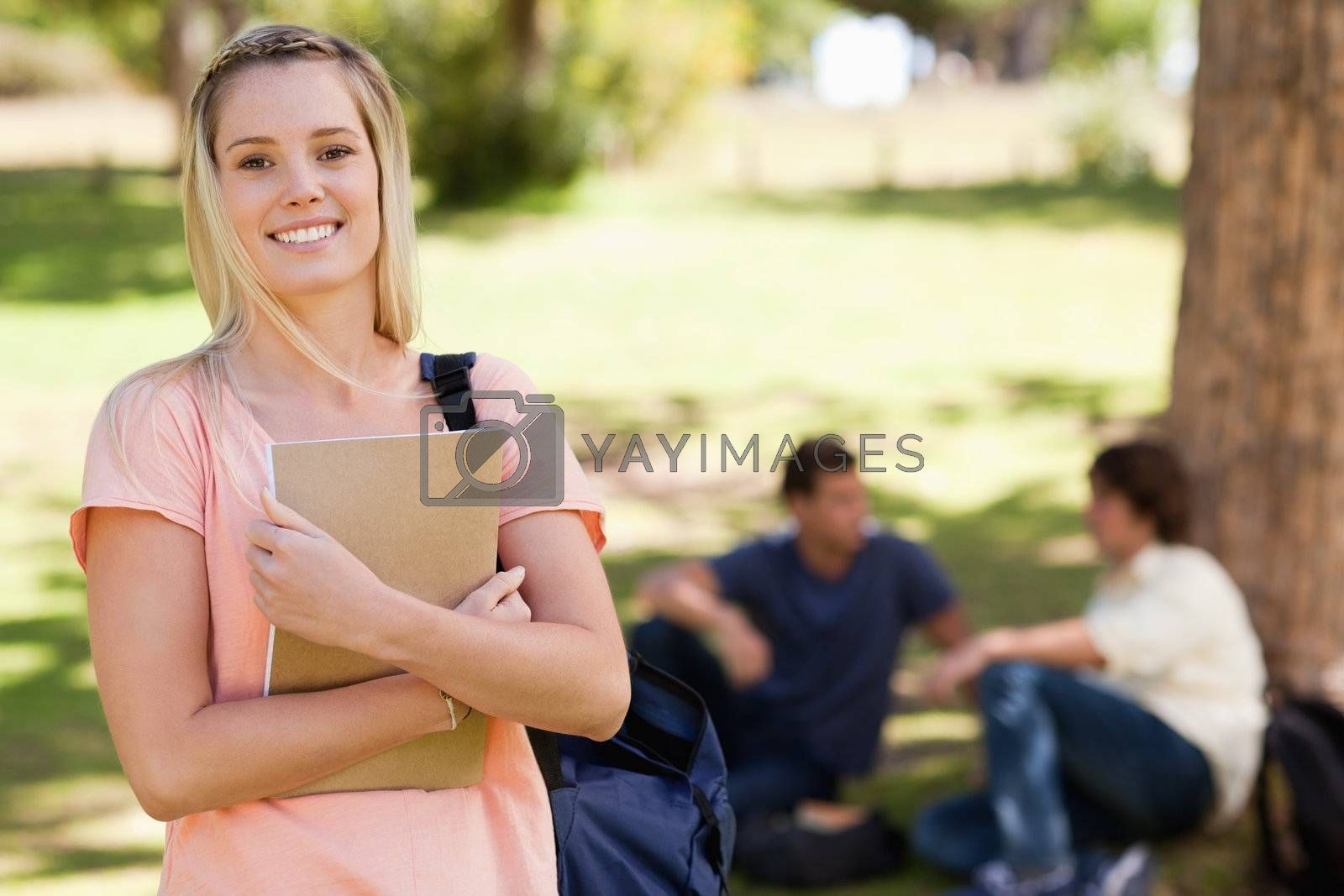Portrait of a pretty girl smiling while holding a textbook in a park with friends in background