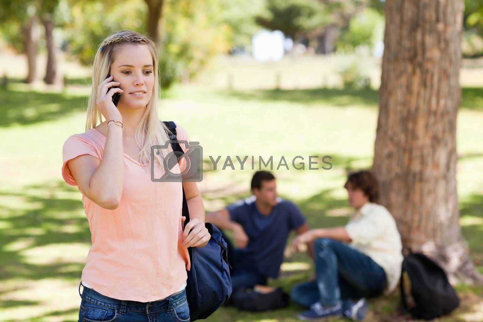 Girl on the phone in a park with friends in background