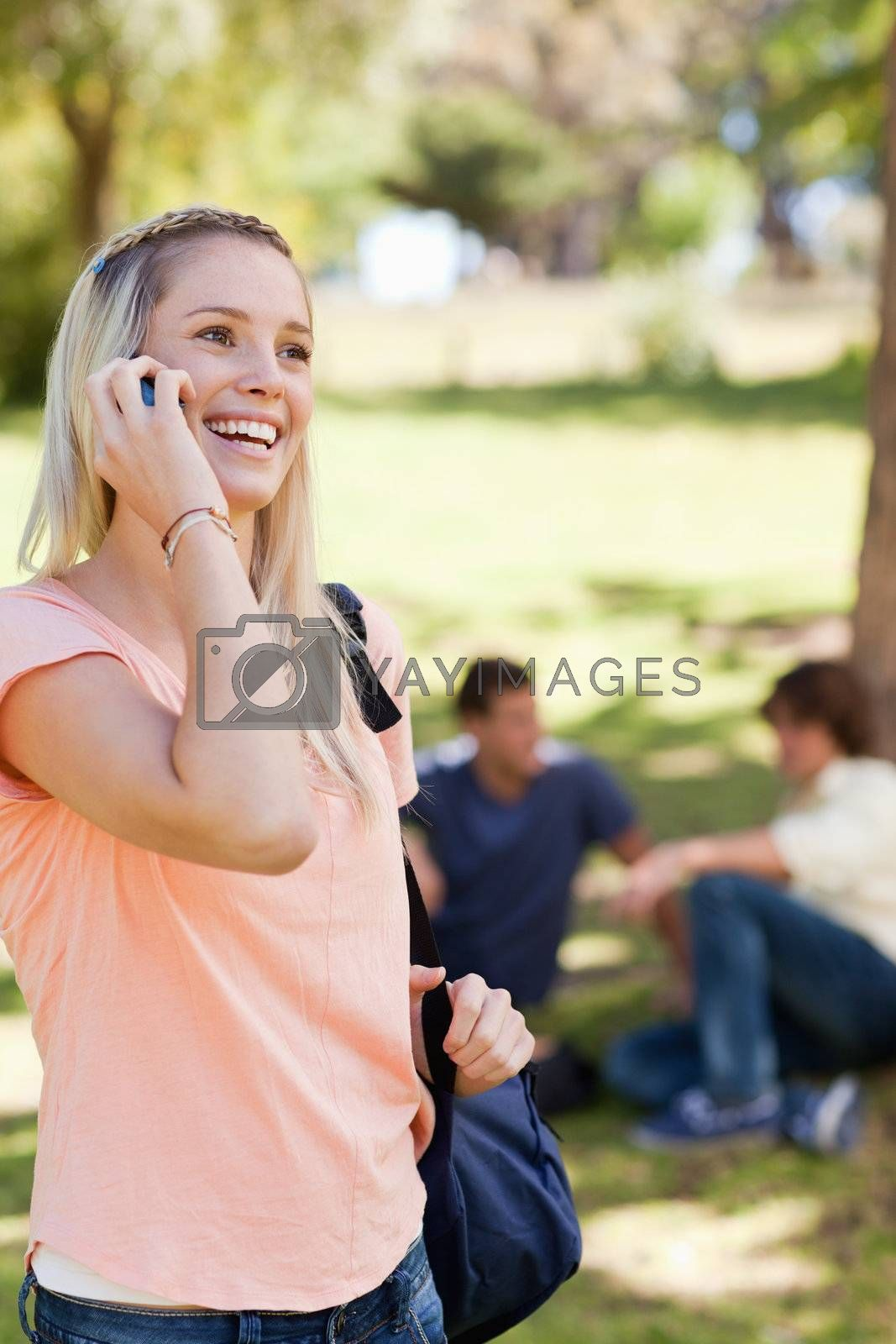 Teenager on the phone in a park with friends in background