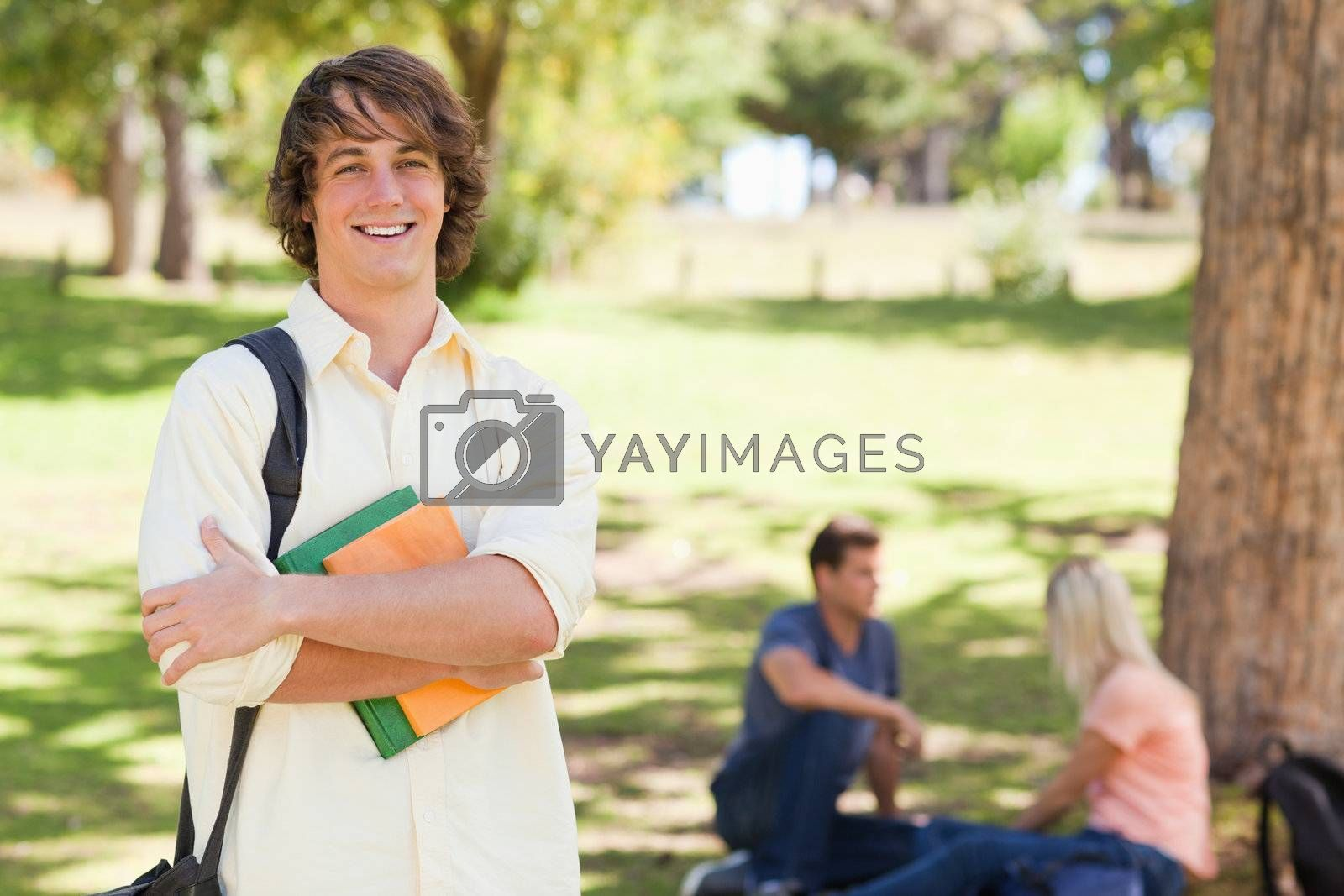 Young man posing with textbook in a park with friends in background